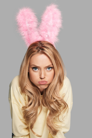 Gelangweiltes Häschen Attraktive junge Frau in den rosa Häschenohren, die ein Gesicht machen und Kamera bei der Stellung gegen grauen Hintergrund betrachten