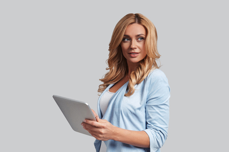 Searching for fresh ideas. Attractive young woman using digital tablet and smiling while standing against grey background