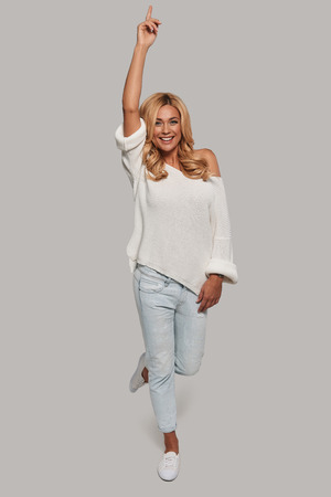 Perfect in every way. Full length of attractive young smiling woman looking at camera and raising one hand while standing against grey background Stock Photo