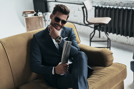 He got candid smile. Handsome young man in full suit keeping hand on chin and smiling while sitting on the sofa Stok Fotoğraf