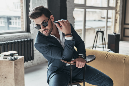 Amazing look! Good looking young man in full suit looking away while sitting on the stool