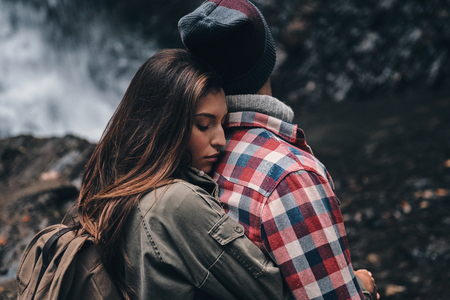 They belong together. Young attractive woman embracing her boyfriend while standing near the waterfall