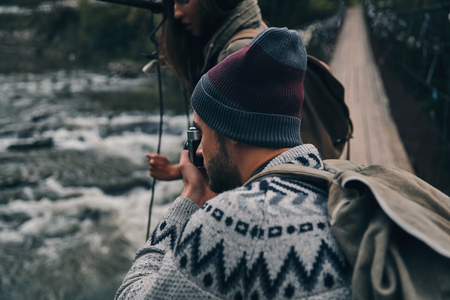 We must capture this! Young modern man photographing the river while standing on the suspension bridge with his girlfriend Stok Fotoğraf