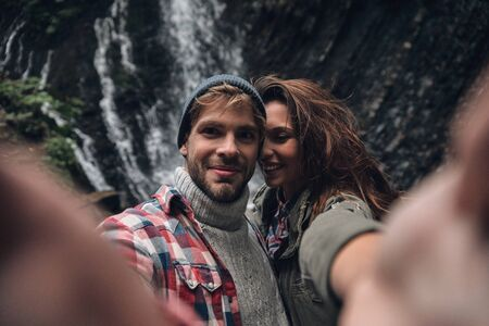 This one goes in frame! Self portrait of beautiful young couple smiling while standing outdoors with the waterfall in the background