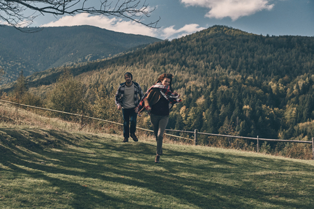 Feels like flying. Full length of happy young couple smiling while running on the valley in mountains outdoors Stock Photo