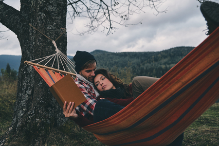 Simple joy of being in love. Beautiful young woman reading a book while lying in hammock with her boyfriend