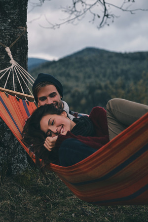 Simply in love. Beautiful young couple embracing and smiling while lying in hammock under the tree