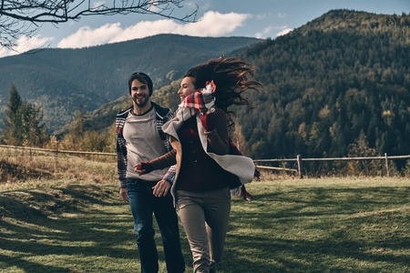 Love inspires them. Happy young couple smiling while running on the valley in mountains outdoors