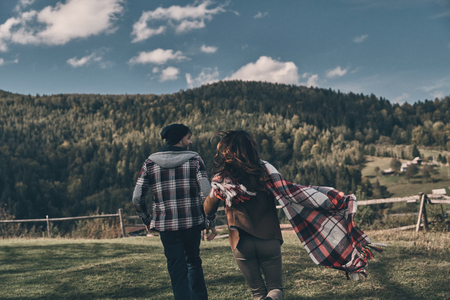 Life is awesome! Rear view of young playful couple running while spending carefree time on the valley in mountains Stock Photo