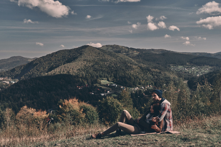 Simply in love.  Beautiful young couple embracing and looking away while lying on the grass in front of the perfect view of mountain range Stock Photo