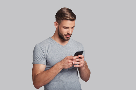 Always online.  Handsome young man holding smart phone and looking at it while standing against grey background