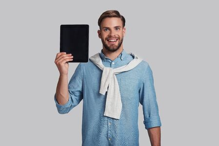Using technologies.  Good looking young man carrying digital tablet and looking at camera with smile while standing against grey background