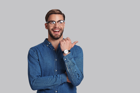 Look over there!  Handsome young man in eyewear pointing copy space and smiling while standing against grey background