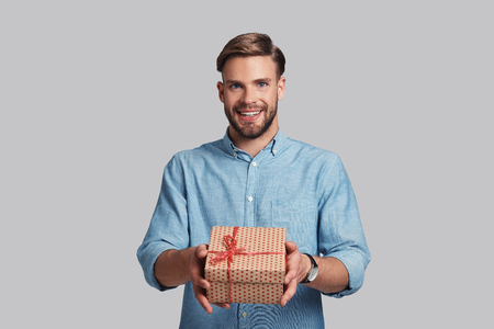 This is for you.  Handsome young man giving gift box and smiling while standing against grey background Reklamní fotografie