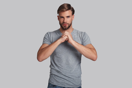Real man. Serious young man looking at camera and making a hand gesture for symbol of courage while standing against grey background Banco de Imagens - 90830930