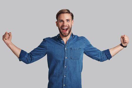 やりました!ハンサムな若い男ジェスチャーと灰色の背景に対して立ちながら笑顔でカメラ目線