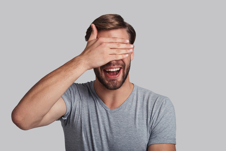 Exited about something. Charming young man covering eyes with hand and smiling while standing against grey background