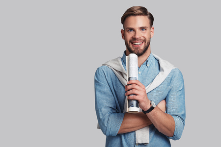 Simply handsome.  Good looking young man carrying a magazine and looking at camera with smile while standing against grey background Reklamní fotografie - 90867717