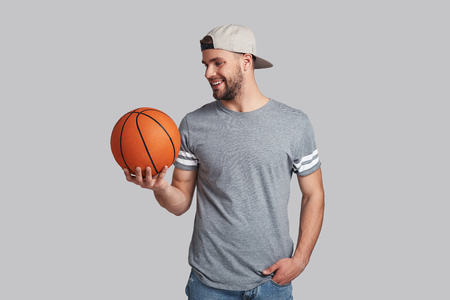 Ready to compete. Handsome young smiling man carrying a basketball ball and looking at it while standing against grey background