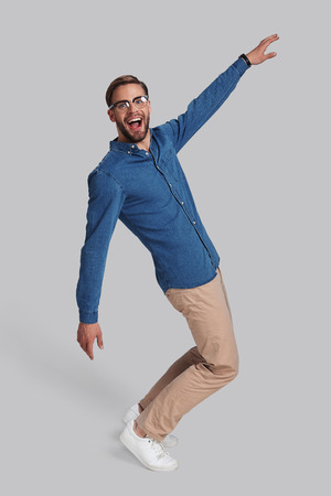 Going crazy. Full length of playful young man dancing and smiling while standing against grey background