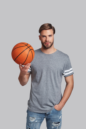 Are you ready to play? Handsome young man carrying a basketball ball and looking at camera while standing against grey background