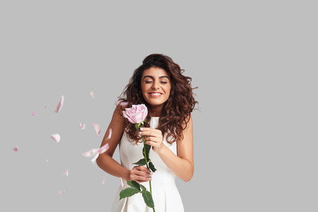 Time for fun! Happy young woman smiling and holding a flower while standing against grey background with rose petals flying around Banco de Imagens
