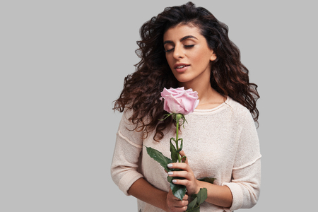 Naturally beautiful. Attractive young smiling woman keeping eyes closed and holding a flower while standing against grey background