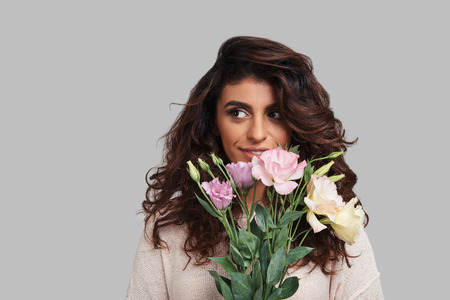 Flowers for her. Attractive young woman holding bunch of flowers and looking away while standing against grey background
