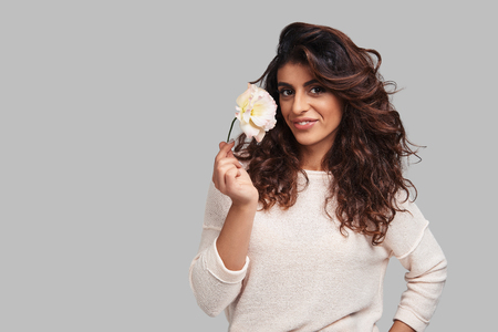 True feminine beauty. Attractive young smiling woman looking at camera and holding a flower while standing against grey background