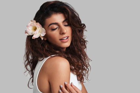 Feeling beautiful. Attractive young woman with a flower in hair keeping eyes closed while standing against grey background Banque d'images