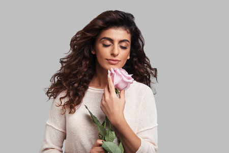 Lost in dreams. Attractive young smiling woman keeping eyes closed and holding a flower while standing against grey background