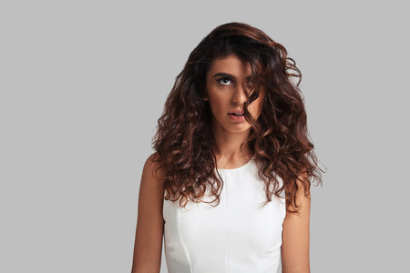 Her hair gives her trouble. Attractive young woman looking away while standing against grey background Banque d'images