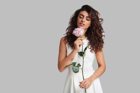 Beautiful perfection. Attractive young smiling woman keeping eyes closed and holding a flower while standing against grey background Reklamní fotografie