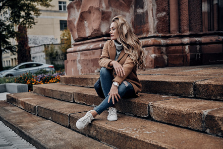 Always in style. Beautiful young woman looking away while sitting on stairs outdoors