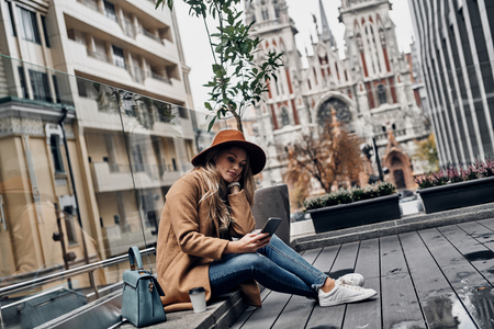 Little coffee break. Attractive young woman in hat and coat using her smart phone while sitting outdoors with church in the background