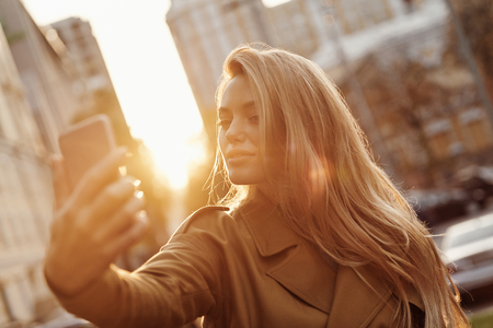 Selfie time! Attractive young smiling woman taking selfie while spending time in the city