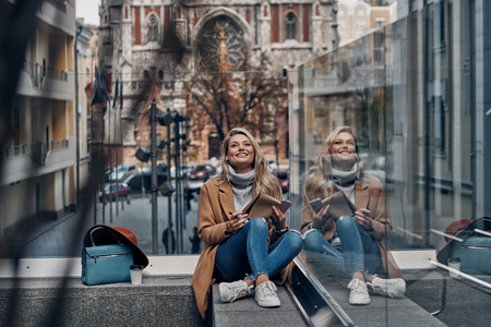 Life is good! Attractive young woman listening music using her smart phone and smiling while spending carefree time in the city Banque d'images