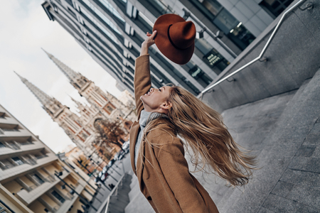 Beauty and style. Attractive young woman holding hat and smiling while spending carefree time in the city