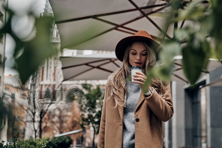 Enjoying hot coffee. Attractive young woman in hat and coat smelling coffee while standing outdoors Banque d'images