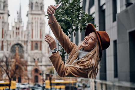 Great look. Attractive young smiling woman in hat and coat taking selfie while spending time in the city