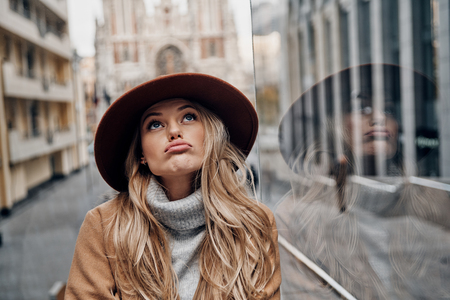 Feeling bored. Attractive young woman in hat and coat making a face and looking away while spending time in the city