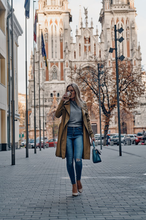 Busy outdoors. Full length of attractive young woman drinking coffee while walking outdoors with church in the background Banque d'images