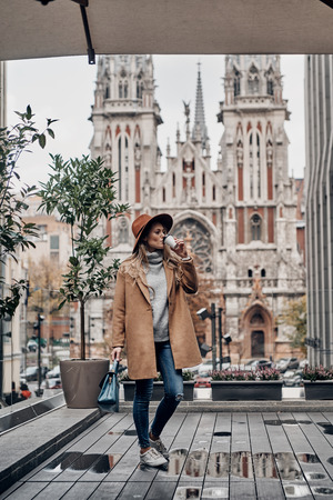 Nothing but fresh coffee. Full length of attractive young woman drinking coffee while standing outdoors with church in the background