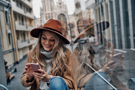 Staying connected. Attractive young woman in hat and coat using her smart phone while spending carefree time in the city