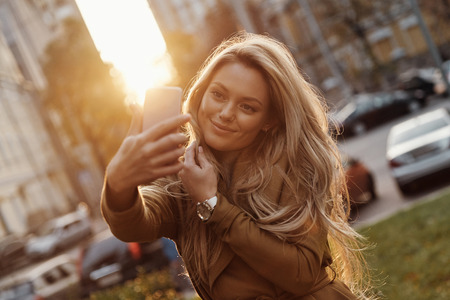 Perfect selfie. Attractive young smiling woman taking selfie while spending time in the city