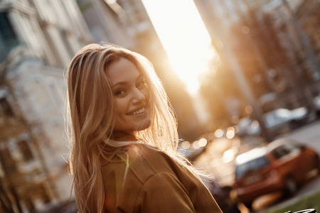 Flirty beauty. Attractive young woman looking at camera and smiling while standing outdoors Standard-Bild