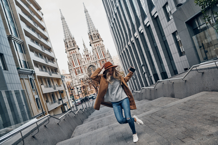 Young and full of energy. Full length of attractive young woman listening music and dancing while spending carefree time in the city Banque d'images