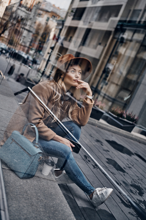 What if... Through the glass case view of thoughtful young woman in hat and coat looking away and smiling while spending time in the city