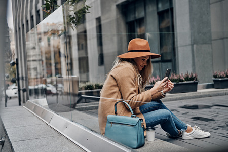 Receiving nice messages. Through the glass case view of attractive young woman in hat and coat using her smart phone while spending carefree time