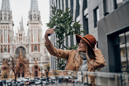 City girl with a great style. Attractive young smiling woman in hat and coat taking selfie while spending time in the city